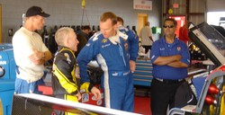 Randy and Mark and Shane in the garage discuss the car and handling, as crew chief Ritchie Howe looks on